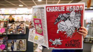 """Une lectrice feuillette """"Charlie Hebdo"""" chez un buraliste, à Lille (Nord), le 25 février 2015. (PHILIPPE HUGUEN / AFP)"""