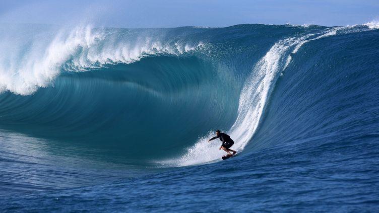 Un surfeur sur la vague géante Teahupoo à Tahiti, en septembre 2014. (GREGORY BOISSY / AFP)