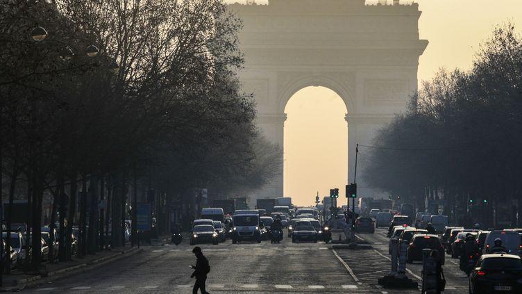 Des voitures circulent près de l'Arc de triomphe, à Paris, un jour de pic de pollution aux particules fines, le 23 janvier 2017. (GEOFFROY VAN DER HASSELT / AFP)