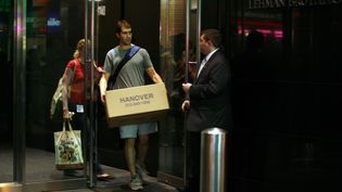 Un employé quitte le batîment de Lehman Brothers à New York avec un carton contenant ses effets personnels le 15 septembre 2008, jour où la banque a été déclarée en faillite. (ORJAN F. ELLINGVAG / CORBIS HISTORICAL)