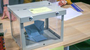 Une urne peu remplie lors du second tour des élections régionales et départementales, à Valence (Drôme), le 27 juin 2021. (NICOLAS GUYONNET / HANS LUCAS / AFP)