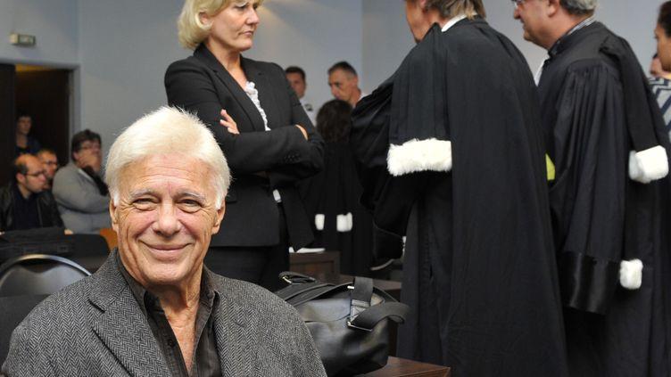 Guy Bedos assis dans l'enceinte dutribunal correctionnel de Nancy (Meurthe-et-Moselle), devant Nadine Morano qui échange avec ses avocats, le 7 septembre 2015. (JEAN-CHRISTOPHE VERHAEGEN / AFP)