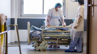 Des infirmières au chevet d'un patient atteint du Covid-19, le 3 décembre 2020, à Limoges (Haute-Vienne). (BURGER / PHANIE / AFP)