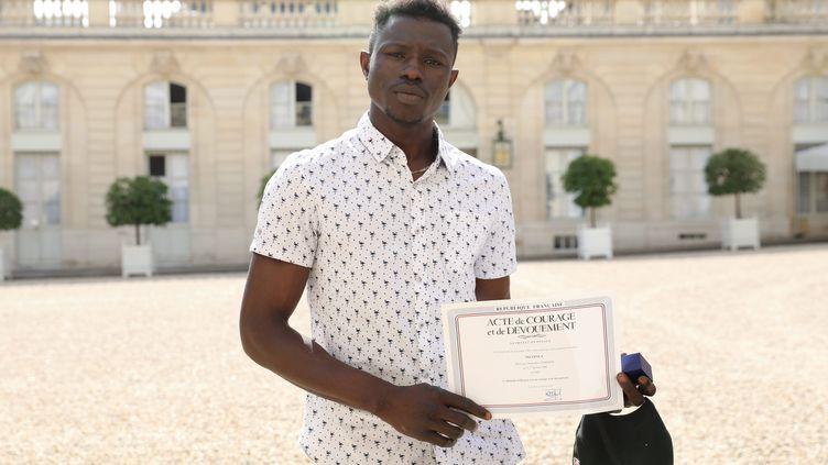 Mamoudou Gassama, dans la cour du palais de l'Elysée, à Paris, le 28 mai 2018. (GUILLAUME GEORGES / MAXPPP)