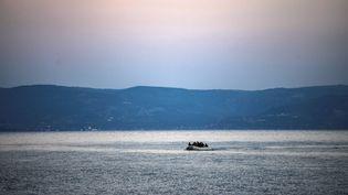 Des migrants à bord d'un bateau sur la mer Méditerranée, près de l'île de Lesbos (Grèce), le 2 mars 2020. (ARIS MESSINIS / AFP)