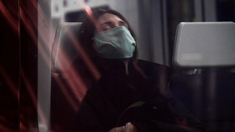 Une femme portant un masque à la fenêtre d'un train, en avril 2020. (JAVIER SORIANO / AFP)