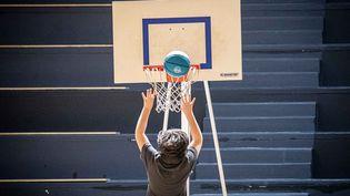Un écolierfait du basket alors qu'il assiste a différentsateliers au Gymnase Stadium dans le 13e arrondissement de Paris lors des jeux sportifs scolaires, le 4 février 2020. (CHRISTOPHE MORIN / MAXPPP)