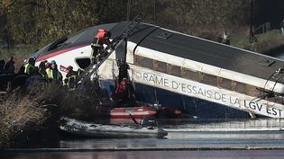 Les secours sur la carcasse du TGV d'essai accidenté, le 15 novembre 2015, dans le canal d'Eckwersheim (Bas-Rhin). (FREDERICK FLORIN / AFP)