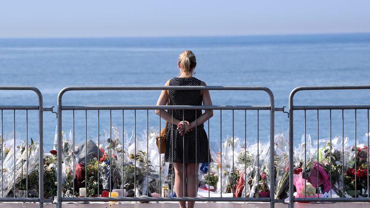 Une femme se tient devant le mémorial dédié aux victimes de l'attentat de Nice, le 16 juillet 2016, sur la promenade des Anglais à Nice (Alpes-Maritimes). (VALERY HACHE / AFP)