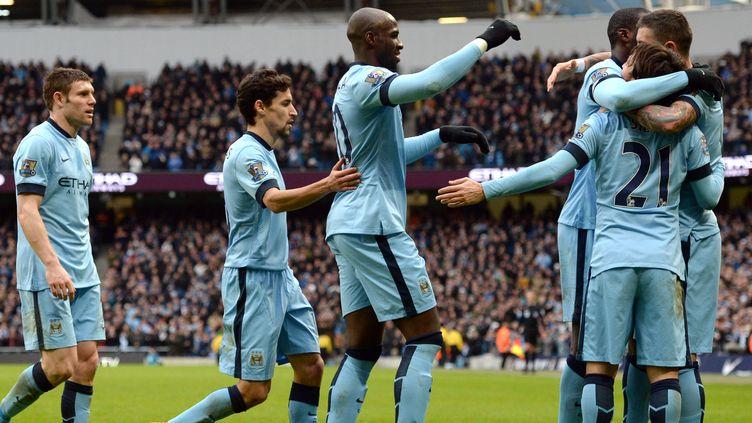 David Silva félicité par ses coéquipiers après l'ouverture du score. (OLI SCARFF / AFP)