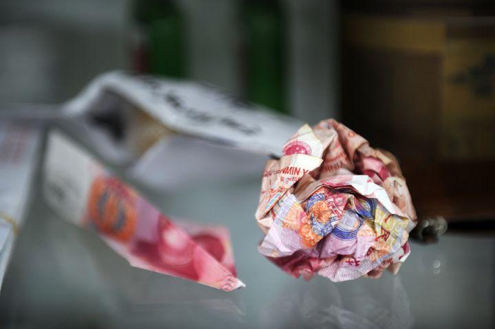 Des billets de 100 yuans roulés en boule avant d'être jetés derrière l'enceinte du studio d'Ai Weiwei, à Pékin, le 9 novembre 2011. (PETER PARKS / AFP)