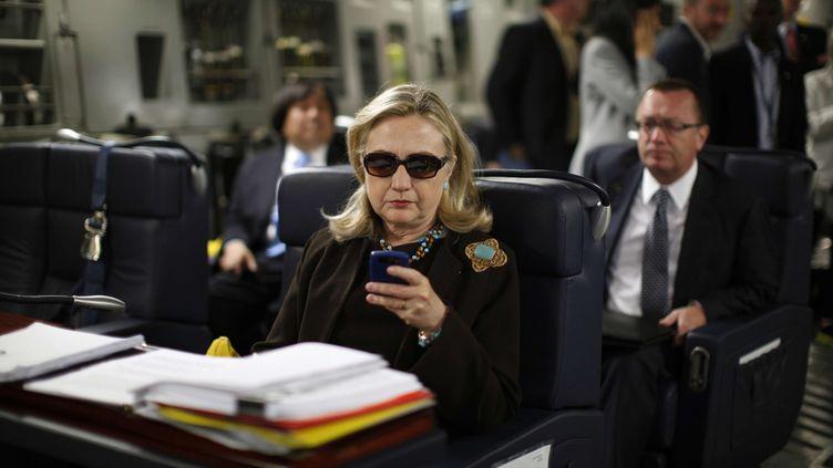 Hillary Clinton, alors secrétaire d'Etat, consulte son téléphone à bord d'un avion au départ de Malte, le 18 octobre 2011. (KEVIN LAMARQUE / AP / SIPA)