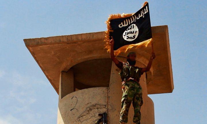Une photo d'un soldat de l'Etat islamique en Irak et au Levant brandissant le drapeau jihadiste, mise en ligne par le site jihadisteWelayat Salahuddin, le 11 juin 2014. (WELAYAT SALAHUDDIN / AFP)