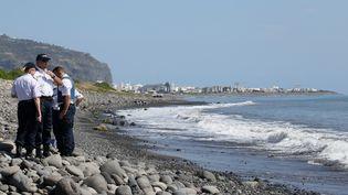A La Réunion, des policiers inspectent des débris métalliques trouvés sur une plage de Saint-Denis, le 2 août 2015. (RICHARD BOUHET / AFP)