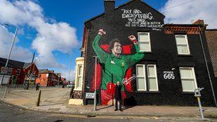 Un fan de Liverpool pose devant la fresque en hommage à l'ancien gardien des Reds Ray Clemence, le 7 octobre 2020 près du stade d'Anfield à Liverpool. (PETER BYRNE / MAXPPP)