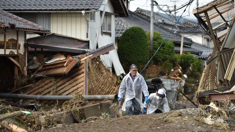 Des habitants marchent dans les décombres des maisons après le passage du typhon Hagibis, le 15 octobre 2019. (KAZUHIRO NOGI / AFP)