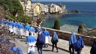Des Chrétiens marchent lors d'une procession pour le Vendredi saint à Brando, en Corse, le 3 avril 2015. Les femmes portent un vêtement bleu traditionnelle, en hommage à la Vierge Marie. (PASCAL POCHARD-CASABIANCA / AFP)