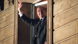 Jacques Chirac salue la foule du balcon de la permanence électorale du RPR, après son élection à la présidence de la République, le 7 mai 1995. (PIERRE BOUSSEL / AFP)