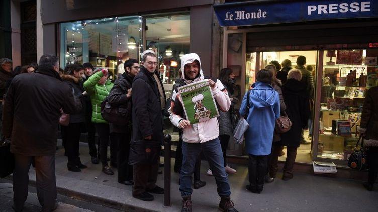 """Un homme pose avec un numéro de """"Charlie Hebdo"""" devant la file d'attente d'un magasin de journaux, le 14 janvier 2015, à Paris. (MARTIN BUREAU / AFP)"""